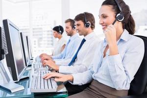 collègues de travail avec des casques d'écoute à l'aide d'ordinateurs photo