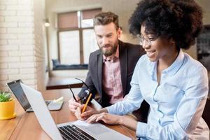 collègues travaillant avec un ordinateur portable à l'intérieur photo