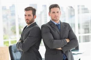 hommes affaires, debout, bras, traversé, bureau photo