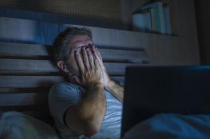 Bourreau de travail attrayant fatigué et stressé travaillant tard dans la nuit épuisé sur le lit occupé avec un ordinateur portable se sentir somnolent et surchargé de travail dans le projet de stress photo