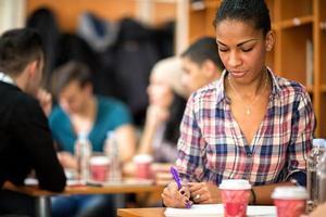 étudiante sud-américaine étudie et écrit sa tâche photo