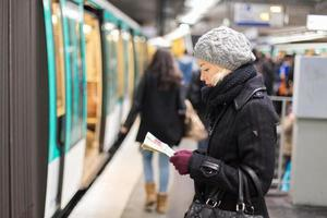 dame attendant sur la plate-forme de la station de métro.