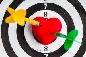 cible noir blanc avec des fléchettes dans l'amour de coeur comme bullseye