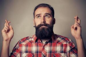 jeune homme faisant un souhait en croisant ses doigts photo
