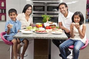 parents indiens asiatiques enfants famille manger des aliments sains dans la cuisine photo
