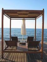 chaises longues et parasol sur le sable près de la mer