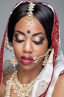 femme indienne en vêtements traditionnels avec maquillage de mariée et bijoux photo