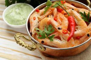 crevettes frites au piment dans une casserole en cuivre, style indien
