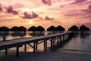coucher de soleil maldives avec silhouette de villas sur l'eau photo