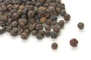 grains de poivre entiers éparpillés sur fond blanc. photo