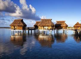 maisons sur l'eau de mer calme et transparente sur un coucher de soleil photo