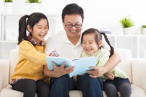 père heureux lire le livre aux enfants