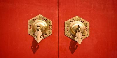 porte antique chinoise rouge avec poignées dorées photo