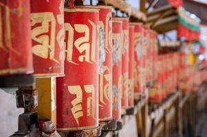 Roues de prière rouges avec inscription prière bouddhiste