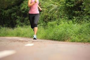 athlète coureur courir sur sentier forestier. photo