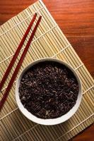 riz à sourcils noirs dans un bol avec des baguettes. photo