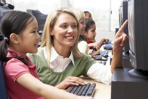 enseignant aidant les enfants de la maternelle photo