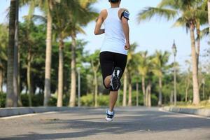 coureur de femme courir sur le sentier du parc tropical photo