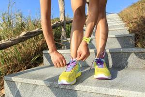 coureur de jeune femme attacher les lacets sur le sentier de pierre photo