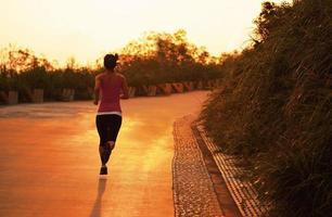 Exercice du matin femme sportive en cours d'exécution sur l'allée de la montagne sous le lever du soleil photo