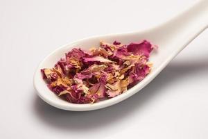 tas de feuilles de rose sec dans une cuillère en céramique blanche