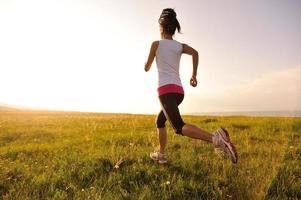 athlète coureur courir sur le champ d'herbe lever / coucher du soleil photo