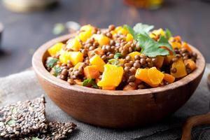 lentilles avec ragoût de carotte et citrouille dans un bol en bois.
