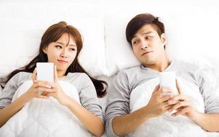 heureux jeune couple dans un lit avec des téléphones intelligents
