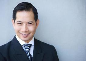homme d'affaires souriant sur fond gris photo