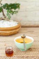 thé vert dans un bol en céramique avec du miel. photo