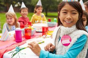 groupe d'enfants ayant une fête d'anniversaire en plein air photo
