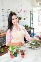 fleuriste travaillant sur terrarium dans son magasin de fleurs au détail vt photo