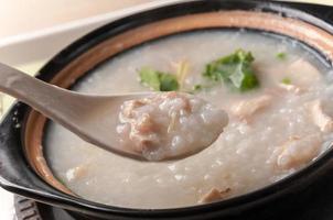 bouillie, ormeau et bouillie de poulet (congee) servis dans un pot en argile photo