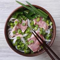 soupe pho bo avec boeuf, nouilles de riz, légumes vue de dessus photo