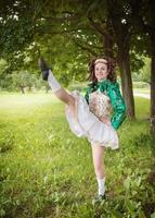 belle jeune fille en robe de danse irlandaise danse en plein air