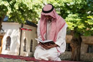homme musulman dans dishdasha lit le coran photo