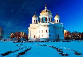 Église orthodoxe blanche avec dômes dorés contre le ciel d'hiver bleu