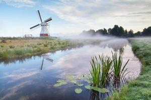Moulin à vent hollandais blanc dans le matin brumeux