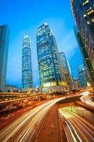 tunnels routiers sentiers lumineux sur les bâtiments de la ville moderne à hongkong photo