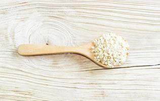 riz brun sur une cuillère en bois avec fond en bois.