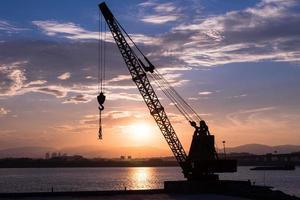 Site de construction sillouhette avec plusieurs grues au coucher du soleil photo