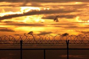 Sécurité silhouette avec une clôture en fil de fer barbelé au coucher du soleil