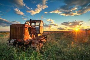 vieux tracteur rouillé dans un champ au coucher du soleil