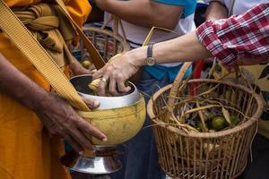 les moines bouddhistes reçoivent des offrandes de nourriture des gens photo
