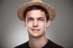 portrait d'un jeune homme normal avec chapeau de paille. photo