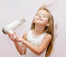 mignonne petite fille souriante sèche les cheveux photo