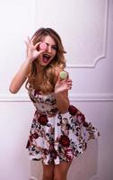 belle femme faire des grimaces avec des macarons en studio photo