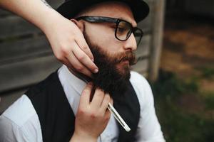 coiffeur rase un homme barbu photo