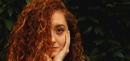 cheveux roux devant des feuilles vertes
