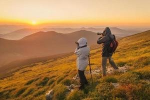 photographes prend un coucher de soleil dans les montagnes photo